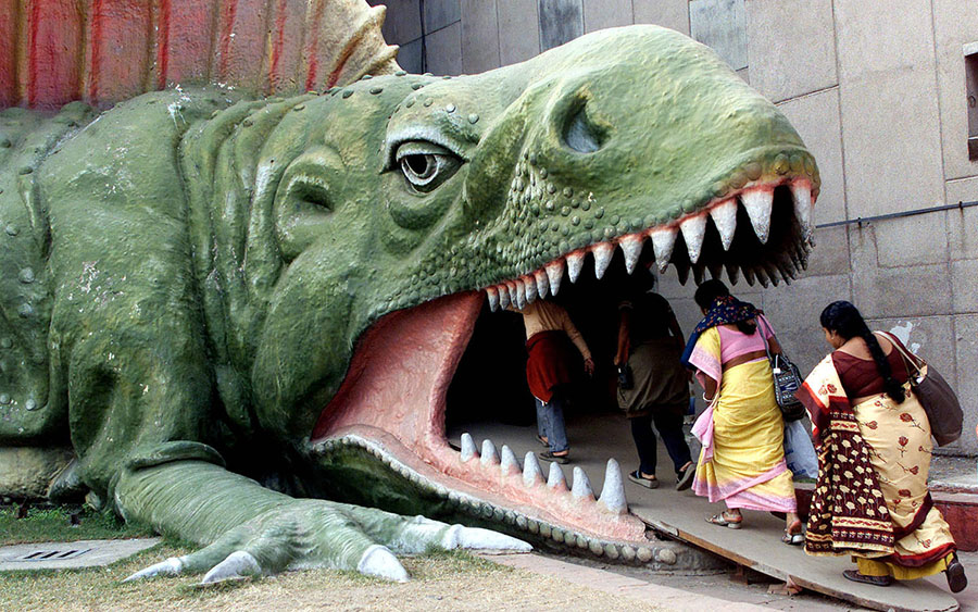Visitors enter the mouth of a dinosaur model at Evolution Park in the eastern Indian city of Calcutta on January 1, 2003. #  Reuters