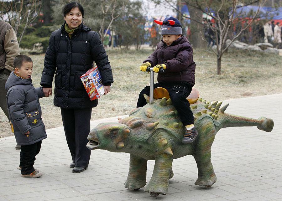 A boy rides a mechanical dinosaur at a park during Spring Festival in Beijing on January 30, 2009. #  Christina Hu / Reuters