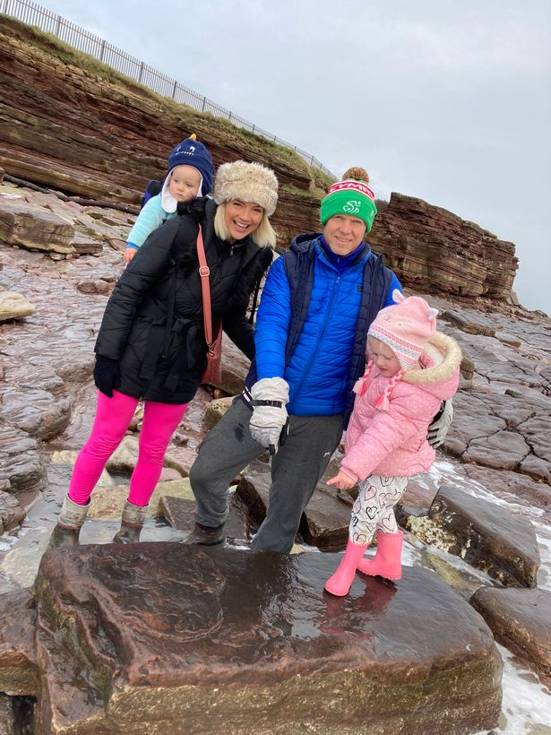 Lily Wilder with her mum Sally and dad Richard and the dinosaur footprint she found on Bendricks Bay Barry