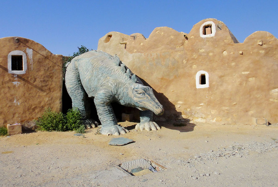 An abandoned building with a dinosaur statue at an old park outside Ksar Ouled Debbab, Tunisia #  Slimstyl / Shutterstock