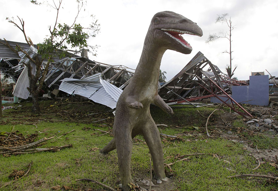 A concrete dinosaur statue stands next to a building destroyed by strong winds brought about at the height of Typhoon Bopha at a playground in New Bataan, southern Philippines, on December 9, 2012. #  Erik De Castro / Reuters