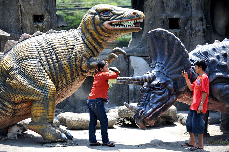 A man takes a photo of a friend beside dinosaur statues at Luneta Park in Manila on May 29, 2010. #  Noel Celis / AFP / Getty