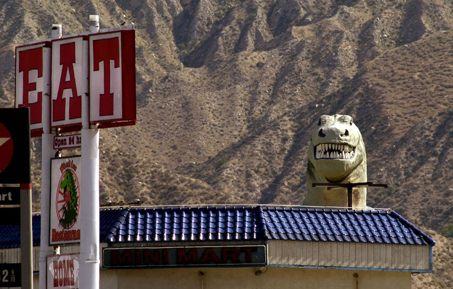 A 60-foot-tall Tyrannosaurus appears behind a restaurant in Cabazon, California, on May 19, 2000. A. The dinosaur is one of two constructed by the late Claude K. Bell as roadside attractions west of Palm Springs. #  David McNew / Newsmakers / Getty