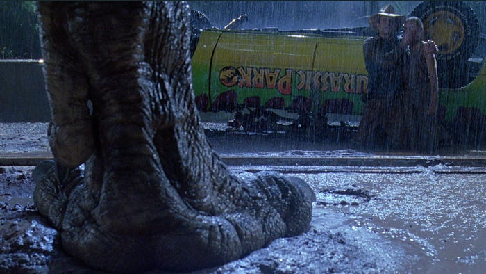 "A T. rex stares down two people in front of an overturned Jeep in ""Jurassic Park."" Universal Pictures"