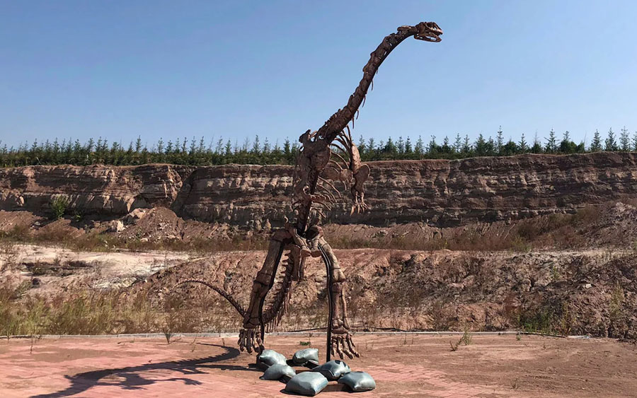 A dinosaur model stands near the site of a future dinosaur museum in Yanji, China CREDIT: AP