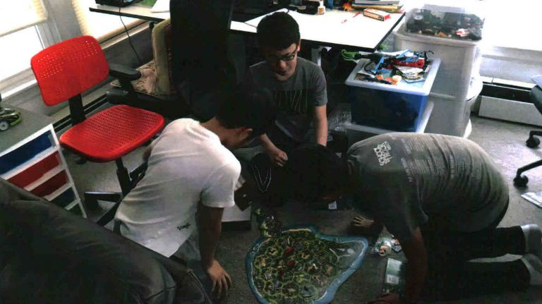 Kidsday reporters Christopher Qu, Kenneth Chang and Justin Tao playing Jurassic Park Danger! board game. Photo Credit: Janet Rumble