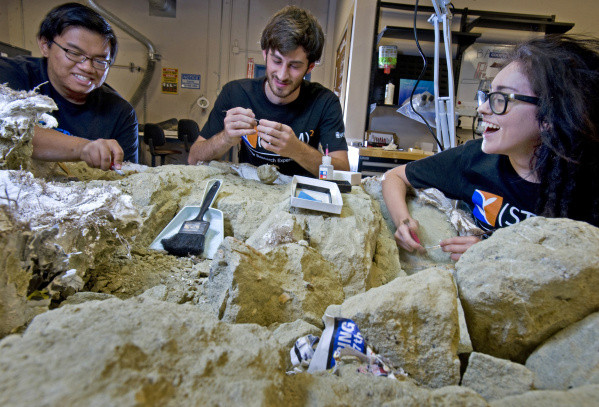Left to right, aspiring paleontologists Gabriel Santos, Daniel Weiherer and Roseanna Garcia work at the John D. Cooper Center Archaeology Lab in Santa Ana.