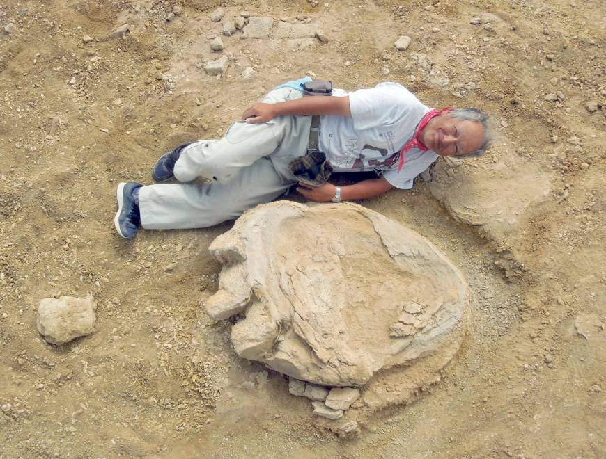 Professor Shinobu Ishigaki lying next to a dinosaur footprint in the Mongolian Gobi Desert