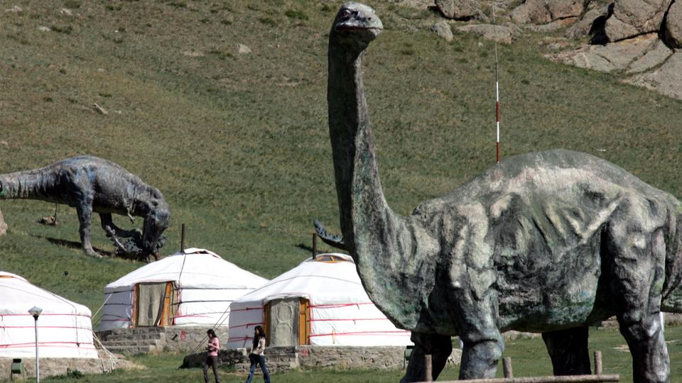 "Visitors to a ""ger"" (tent) camp walk past large dinosaur sculptures used as a gimmick to promote the camp at the Terelj National Park near Ulan Bator, Mongolia. May 27, 2005. (File Photo /AP Archive)"