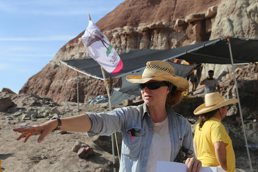 Dr. Alyssa Bell points to where the bone that led to the quarry was discovered. The quarry is the tented area in the background, where researchers dig into the side of a hill to find more bones. CREDIT KATE GROETZINGER / KUER