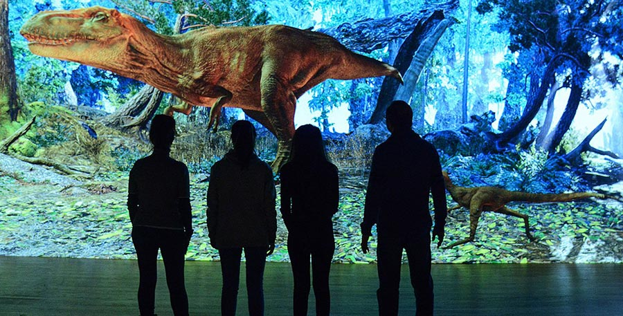 Visitors encounter a massive animated projection of a t. rex and its offspring in a late cretaceous setting. the huge dinosaur will react to visitors, leaving them to wonder, 'did that t. rex see me?' image © AMNH /r. mickens