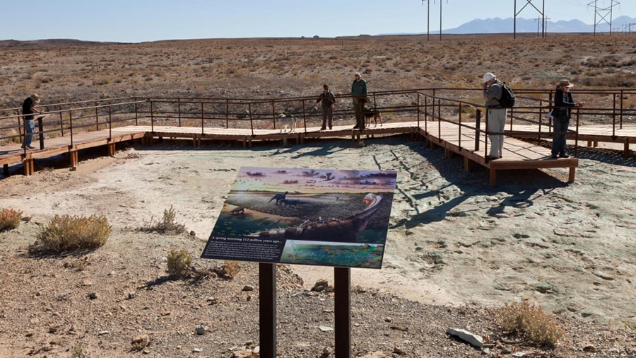 Visitors to the Mill Canyon dinosaur track site can walk along an elevated boardwalk above Early Cretaceous-era tracks and contemplate illustrations such as this one by artist Brian Engh. Alamy